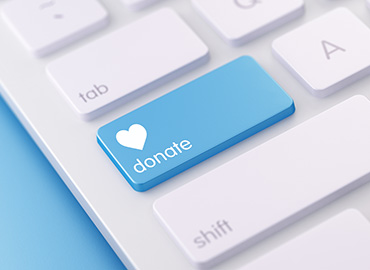 "A white keyboard in which the caps lock key has been replaced with a blue button with the word ""Donate"" and a heart in white on it."